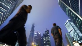 Pedestrians walk past commercial buildings including the Shanghai Tower, center left, as it stands under construction at night in the Lujiazui district of Shanghai, China, on Friday, June 28, 2013. China's President Xi Jinping said officials shouldn't be judged solely on their record in boosting gross domestic product, the latest signal that policy makers are prepared to tolerate slower economic expansion. Photographer: Tomohiro Ohsumi/Bloomberg