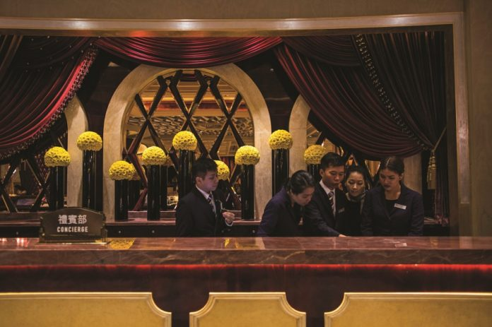 Employees stand at the concierge desk at Studio City casino resort, developed by Melco Crown Entertainment Ltd., in Macau, China, on Tuesday, Oct. 27, 2015. Studio City is the latest test of the former Portuguese colony's ability to attract visitors wanting to play on more than gaming tables and slot machines. Photographer: Justin Chin/Bloomberg