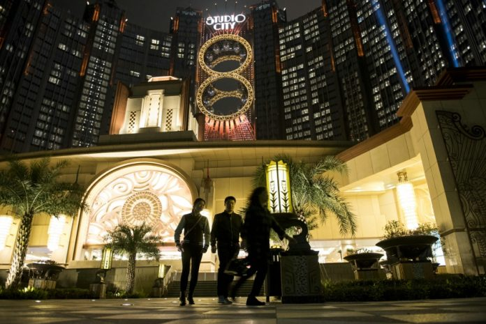 Pedestrians walk past Studio City casino resort, developed by Melco Crown Entertainment Ltd., illuminated at night in Macau, China, on Tuesday, Feb. 16, 2016. Mainland Chinese tourists poured into Macau in greater numbers during the week-long Lunar New Year holiday, even as many shunned neighboring Hong Kong again this year, but gambling revenues extended an almost two-year slump as high-rollers stayed home. Photographer: Xaume Olleros/Bloomberg