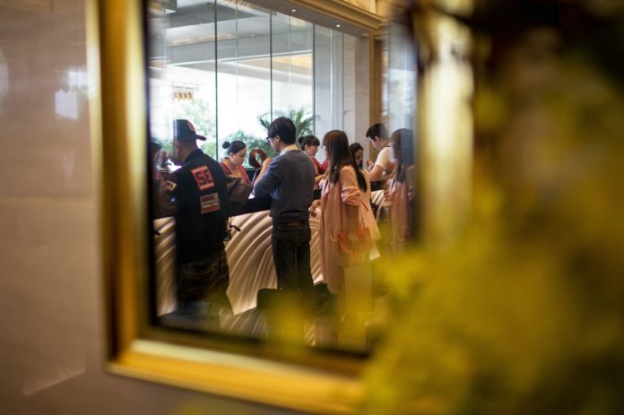 Guests are reflected in a mirror while standing at a check-in counter in the lobby of the Galaxy Macau casino resort, operated by Galaxy Entertainment Group Ltd., in Macau, China, on Monday, Mar. 16, 2015. Galaxy, the Macau casino operator that made Lui Che-woo Asia's second-richest person, is scheduled to report earnings on March 19. Photographer: Billy H.C. Kwok/Bloomberg